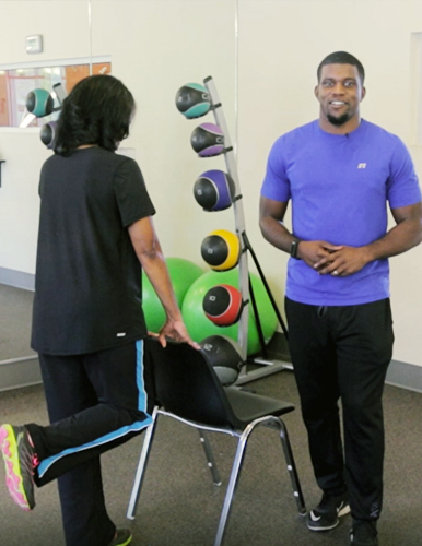 woman lifting leg with support of a chair in a gym with man looking at the camera next to her