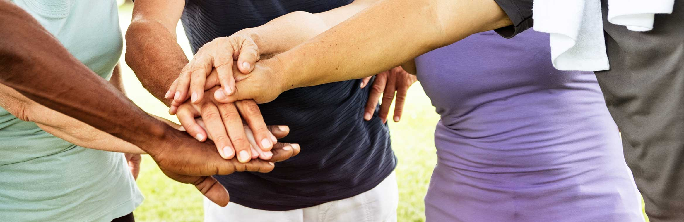 group of hands together outside.
