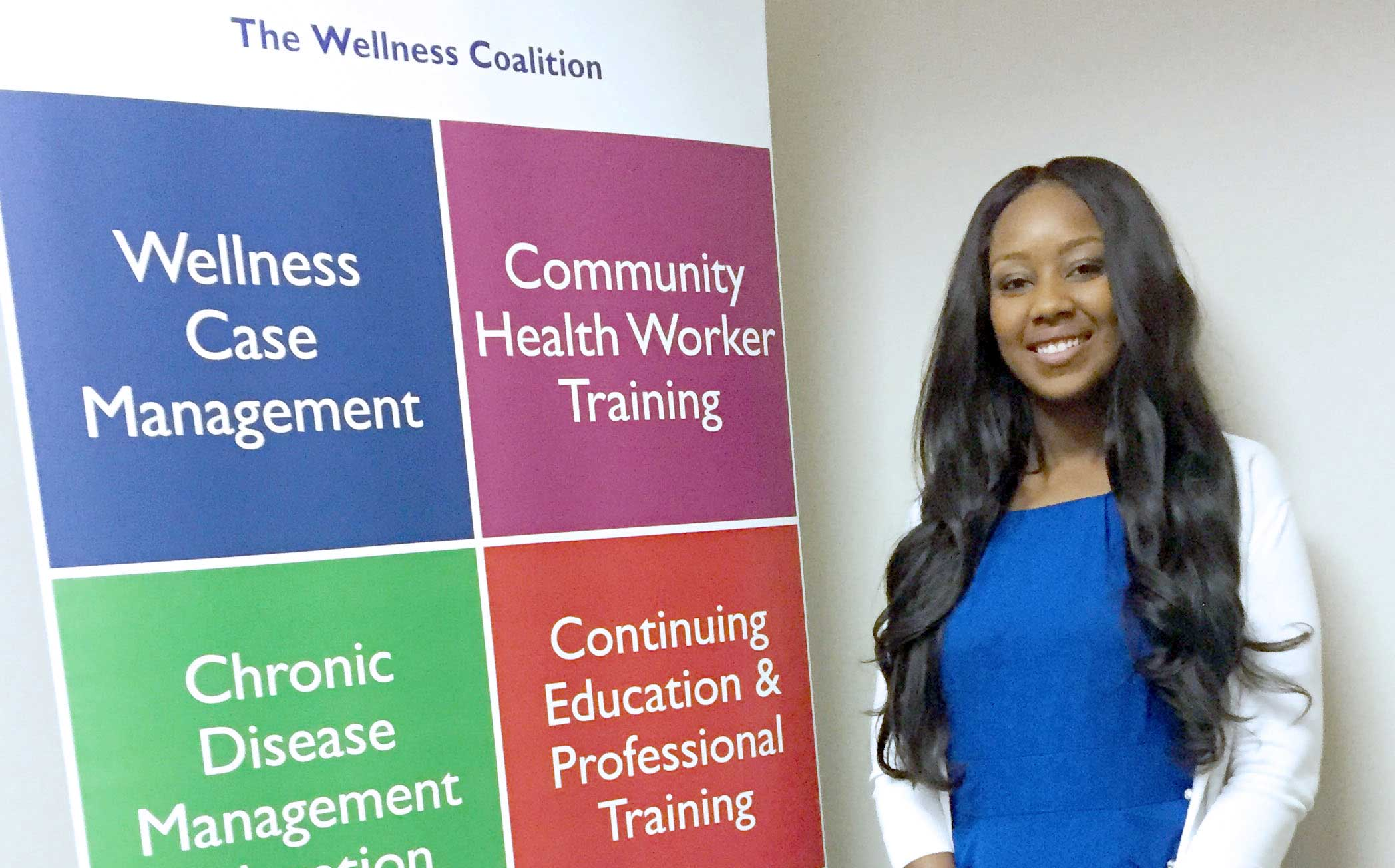 woman standing next to a colorful posterboard for wellness coalition