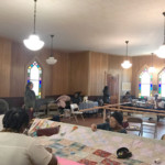 people quilting inside of a church