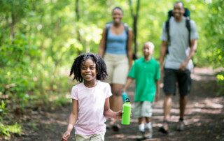 African-American family hiking in woods, with little girl walking in font smiling with water bottle.