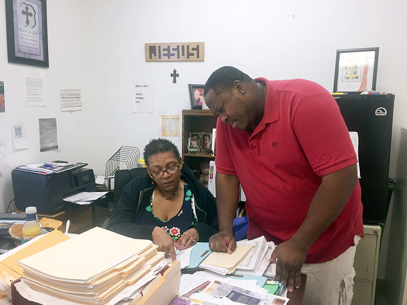 Case manager, Sophia Dowdell, showing a man something in a file at a desk.